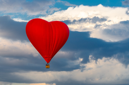 Red hot air balloon in the form of heart in the sky. Imagens