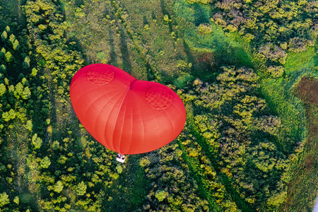heart balloon: Red balloon in the form of heart over green fields and forests Stock Photo