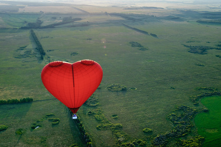 extremes: Red balloon in the form of heart over green fields and forests Stock Photo