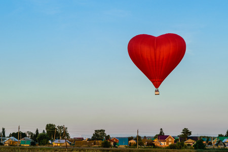 Red balloon in the form of heart flying above the village