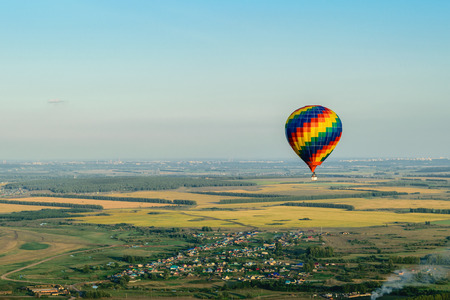 Colorful hot air balloon flying over the village, forest and fields Stock Photo