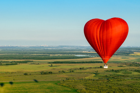 Red balloon in the form of heart over green fields and forests Imagens