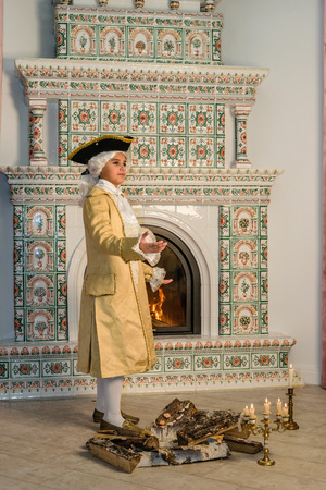 three cornered: Boy in vintage costume near the fireplace