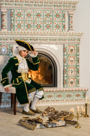 tricorn hat: Boy in vintage costume near the fireplace