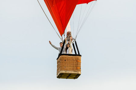 flying man: Man and woman flying in the hot air balloon Stock Photo