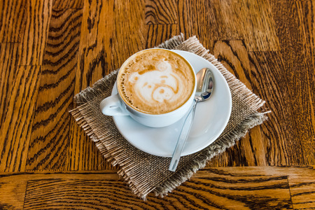 Cup of cappuccino coffee on a wooden table