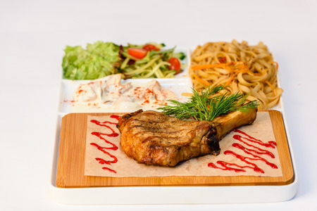 Meat chops with grilled ribs with pasta and vegetables Stock Photo