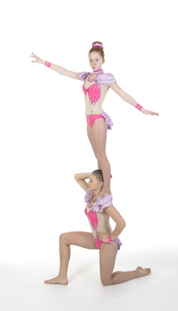 Studio filming two girls performing acrobatics. Studio shot on white background,isolated image. Editorial