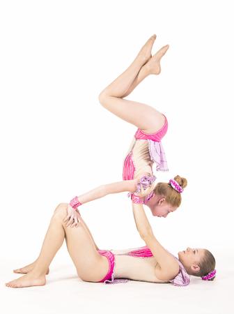 gogo girl: Studio filming two girls performing acrobatics. Studio shot on white background,isolated image. Editorial