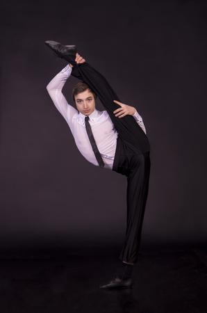 Gimnasta extraordinaria en un fondo negro. El hombre sin huesos. Fotografía de estudio de artistas de circo.