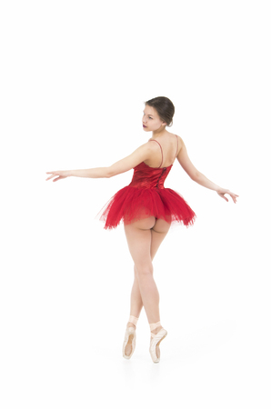 A girl in a red tutu dancing ballet. Studio shot on white background, isolated image.