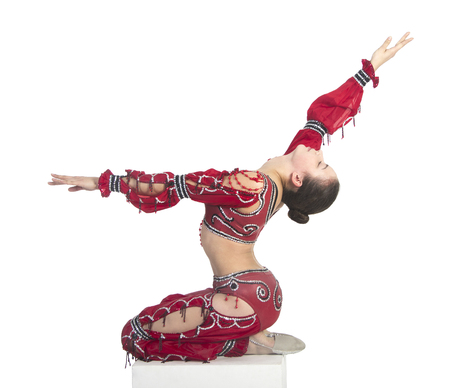 Acrobat does gymnastic exercises , the isolated image on a white background. Young athletic woman in a red leotard, practicing acrobatics. Stock Photo