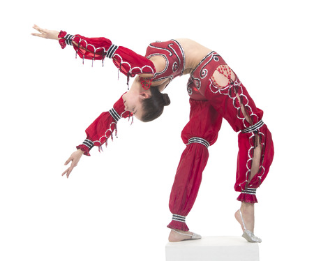 etalon: Acrobat does gymnastic exercises , the isolated image on a white background. Young athletic woman in a red leotard, practicing acrobatics. Stock Photo
