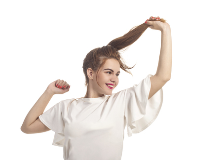 Girl in summer dress plays with hair posing in Studio on a white background.Isolated images,Studio photography. Stock Photo