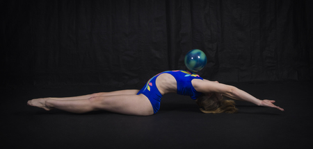 Gymnast performs exercises with the ball. Studio shot on dark background. Standard-Bild