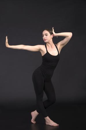 Girl in leotard dancing to contemporary choreography. Studio shot on dark background.