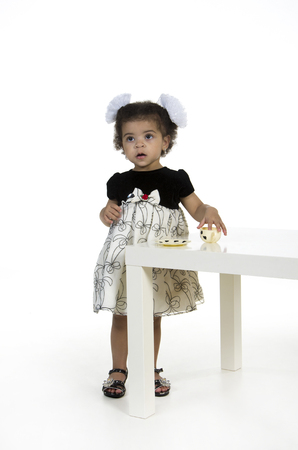 Little girl playing with a tea set on the table.Studio photography on a white background, isolated image. Stock Photo