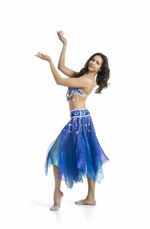 Niña sonriente bailando la danza oriental. La actuación en la etapa de danza del vientre. Disparos en estudio en imagen aislada de fondo blanco.