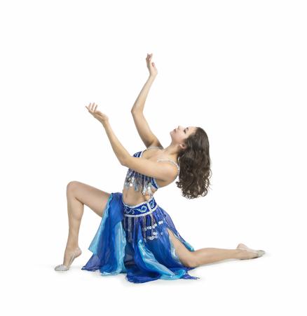 Menina de sorriso que dança a dança oriental. O desempenho na dança de barriga do estágio. O tiro no estúdio no fundo branco isolou a imagem.