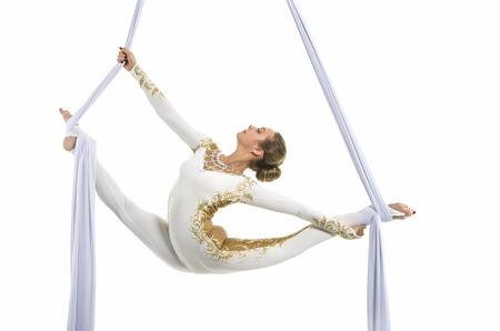 Mujer bonita - aerialista realizando trucos aéreos en sedas aéreas. Estudio de disparos sobre un fondo blanco. Foto de archivo