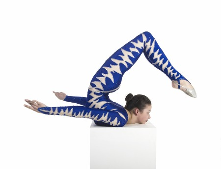 Acrobat does gymnastics, isolated image on a white background. A young circus artist in a blue suit , performs acrobatic elements.
