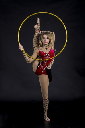 The contortionist girl in stage costume with hoops. Studio shot on dark background.