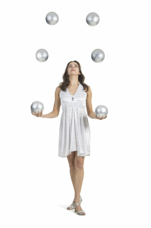 A young female circus performer, juggles silver balls. Studio shot on white background, isolated image. Stock Photo