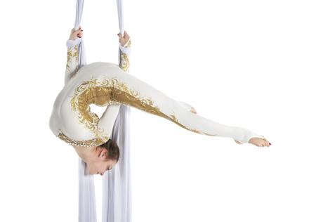 Pretty woman - aerialist performing aerial tricks on aerial silks. Studio shooting on a white background.