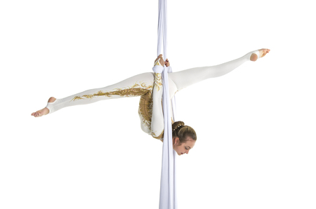 Pretty woman - aerialist performing aerial tricks on aerial silks. Studio shooting on a white background.