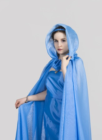 The girl in the blue tunic and cloak,in the Greek style, posing on a gray background. Studio shot, isolated image. 스톡 콘텐츠
