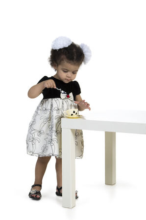 Little girl playing with a tea set on the table.Studio photography on white background, isolated image. Stock Photo