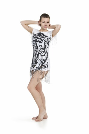 A young woman with bobbed hair in a dress with tiger print posing barefoot on a white background. Studio shot, isolated image.