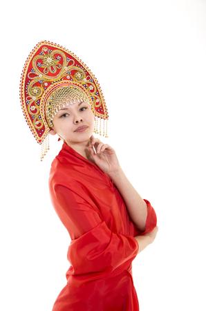 Portrait of smiling girl in kokoshnik (headdress) and red dress on white background.