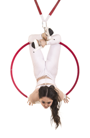 A young girl performs the acrobatic elements in the air ring. Studio shooting performances on a white background. Stock Photo