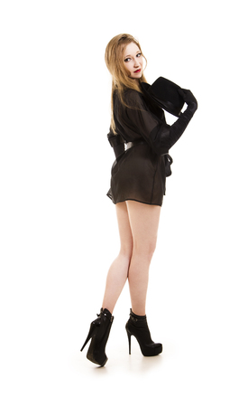 Beautiful young girl in black tunic, black hat and black shoes.Posing in Studio on white background isolated image. Stock Photo