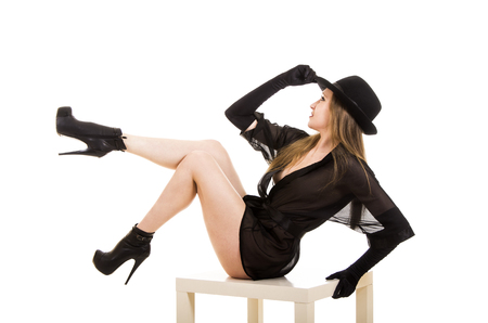 Beautiful young girl in black tunic, black hat and black shoes.Posing in Studio on white background isolated image. 免版税图像