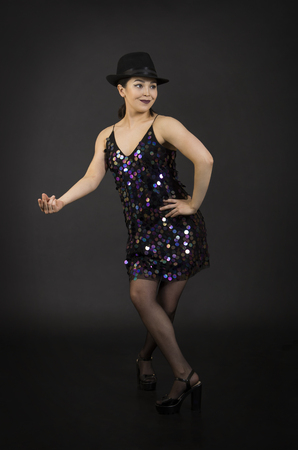 A young woman in a hat dancing.Studio shooting on a dark background.