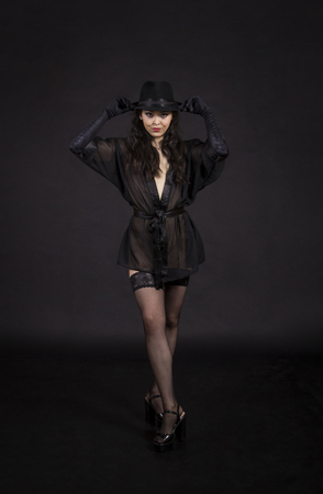 Beautiful young girl dancing in black tunic, black gloves and black hat.Posing in the Studio on a dark background, isolated images. 免版税图像