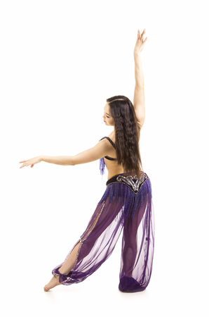 Attractive brunette girl with long hair dancing belly dance. on isolated white background. Standard-Bild