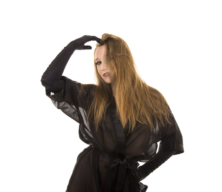 Beautiful young girl in black tunic and black gloves.Posing in Studio on white background isolated image. 免版税图像