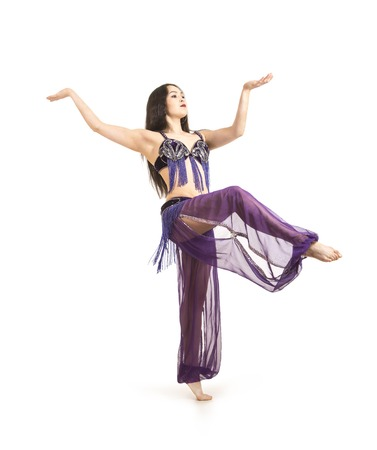 Attractive brunette girl with long hair dancing belly dance. on isolated white background. Foto de archivo