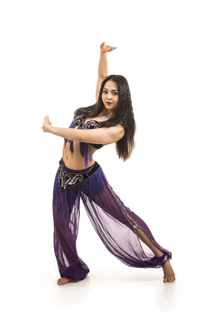 Attractive brunette girl with long hair dancing belly dance. Isolated on a white background.