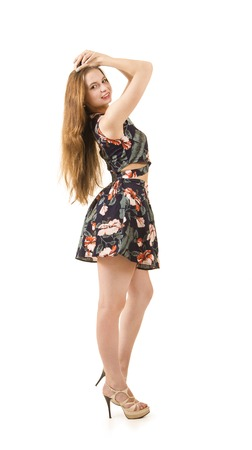 A young girl with long hair and a short dress.Studio shooting on white background, isolated image