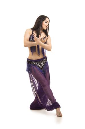 Attraktives brünettes Mädchen mit langem Haar, das Bauchtanz tanzt. auf isoliertem weißem Hintergrund.