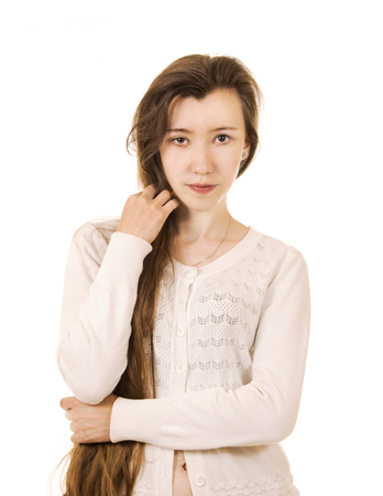 Emotions of a beautiful girl with long hair, in a white jacket posing in Studio on a white background. The isolated image.