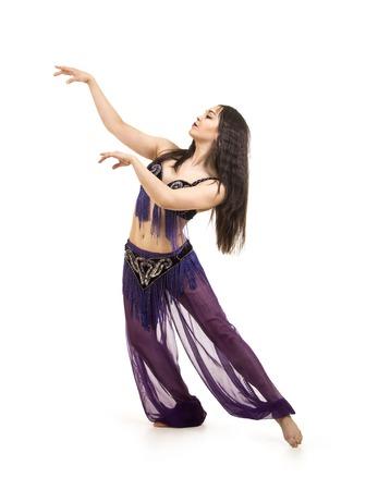 Attraktives brünettes Mädchen mit langem Haar, das Bauchtanz tanzt. auf isoliertem weißem Hintergrund. Standard-Bild