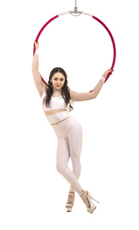 A young girl performs the acrobatic elements in the air ring. Studio shooting performances on a white background. Banque d'images