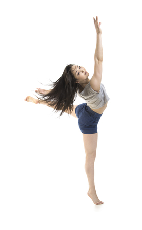 A young girl in shorts and a t-shirt dancing modern ballet. Studio shot on white background. The isolated image. Foto de archivo