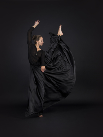 A young,smiling girl in black suit dancing modern choreography.Studio shot on dark background, isolated image.