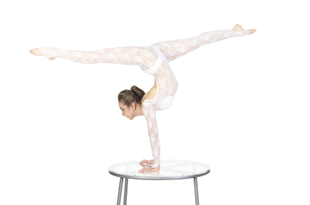 Acrobat doing gymnastics, a young athlete in a white suit with rhinestones, practicing acrobatics. Isolated image on white background.